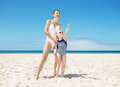 Happy mother and child pointing to somewhere at sandy beach Royalty Free Stock Photo
