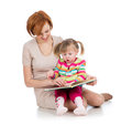 Happy mother and child read a book together Stock Images