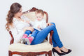 Happy mother and child sitting at armchair home mum looking baby girl fashion baby clothes jeans boots shoes mothercare is most Stock Photo