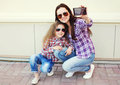 Happy mother and child taking self-portrait on smartphone