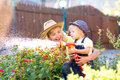 Happy mother and child water in domestic garden