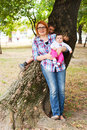 Happy mother with children in a park leaning against tree Stock Photography