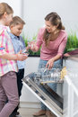 Happy mother and children placing glasses in dishwasher Royalty Free Stock Photo