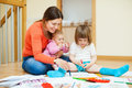Happy mother with children plays at home