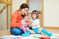 Happy mother with children plays toys at home interior Royalty Free Stock Photography