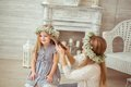 A happy mother is combing her daughter s hair they are in the light room and both having floral wreathes on the atmosphere of Stock Image