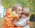 Happy mother and daughter in autumn smiling leaves park Royalty Free Stock Photo