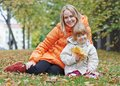 Happy mother and daughter in autumn smiling leaves park Stock Image