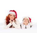 A happy mother and a daughter in christmas hats the image is isolated on white background Stock Photo