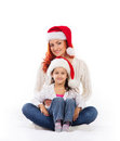 A happy mother and a daughter in christmas hats the image is isolated on white background Royalty Free Stock Image