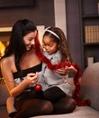 Happy mother and daughter at christmas little afro sitting on sofa holding decoration smiling Stock Photo