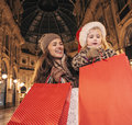 Mother and child in Christmas hat with shopping bags in Milan