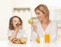 Happy mother and daughter eating breakfast people healthy lifestyle family food concept healthy over home kitchen background Royalty Free Stock Photos