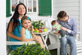 Happy mother with daughter and father with son sit at table white next to their house focus on women girl Stock Photos