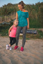 Happy mother and daughter in fitness gear standing on beach a young wearing is looking down lovingly at her who is leaning against Royalty Free Stock Image