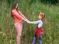Happy mother and daughter holding hands and looking at each other against the background of tall grass Stock Photo