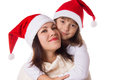 Happy mother and daughter hugging in christmas hats over white Stock Image