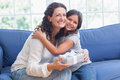Happy mother and daughter hugging and smiling at camera in the living room Royalty Free Stock Images