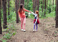 Happy mother and daughter looking at each other holding hands while walking on a forest path Royalty Free Stock Images