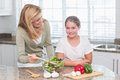 Happy mother and daughter preparing salad together at home in the kitchen Royalty Free Stock Image