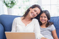 Happy mother and daughter sitting on the couch and using laptop in living room Stock Photo