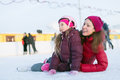 Happy mother and daughter sitting on the outdoor rink skating in winter Stock Images