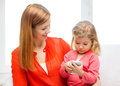 Happy mother and daughter with smartphone at home family children parenthood technology internet concept Stock Photos