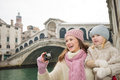 Happy mother and daughter taking photos near rialto bridge modern family a winter break to enjoy inspirational adventure in venice Stock Photo