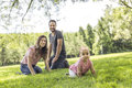 Happy mother, father and daughter in the park. Beauty nature scene with family outdoor lifestyle Royalty Free Stock Photo