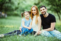 Happy mother, father and daughter playing in the park. Beauty nature scene with family outdoor lifestyle. Happy family resting tog Royalty Free Stock Photo