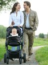 Happy mother and father smiling and pushing baby pram with child portrait of a Stock Photography