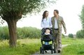 Happy mother and father walking with baby in pram Royalty Free Stock Photo