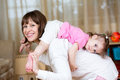 Happy mother having fun holding her daughter on back at home Stock Photo