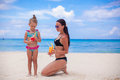 Happy mother and her adorable little daughter with juice at tropical beach this image has attached release Stock Photo