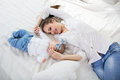 Happy mother with her baby girl in bed young are lying on Stock Images