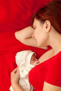 Happy mother and her baby sleeping in bed the concept of maternal love care happiness pacification Stock Photography