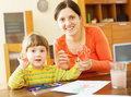 Happy mother and her child painting with handprinting on paper focus on woman Royalty Free Stock Image