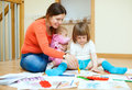 Happy mother and her children drawing on paper at parquet floor at home Stock Photos