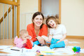 Happy mother and her children plays at parquet floor Royalty Free Stock Images