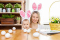 Happy mother and her cute child wearing bunny ears, getting ready for Easter