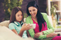 Happy mother and her cute teen daughter are looking at mobile phone