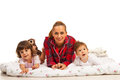 Happy mother and her kids in bed lying with little against white background Royalty Free Stock Photography