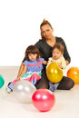 Happy mother and her kids sitting down on floor with balloons Stock Photo