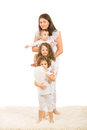 Happy mother with her kids and three standing on carpet home in a line isolated on white background Royalty Free Stock Images