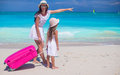 Happy mother and her little daughter with luggage on tropical white beach Royalty Free Stock Photo