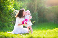 Happy mother and her sweet daughter in the garden beautiful young nd adorable little cute little curly girl a white dress playing Stock Photo