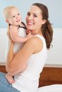 Happy mother holding and playing with cute smiling baby close up portrait of a Stock Photos