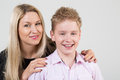 Happy mother hugging smiling son with disheveled hair in the studio Royalty Free Stock Photos