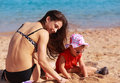 Happy mother and kid girl playing in sand on the beach Stock Images
