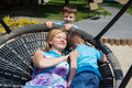 Happy mother with kids in swing laying saucer outdoor Stock Photo